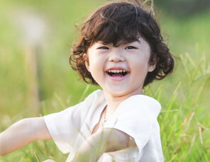 asiatischer Junge spielt im Gras
