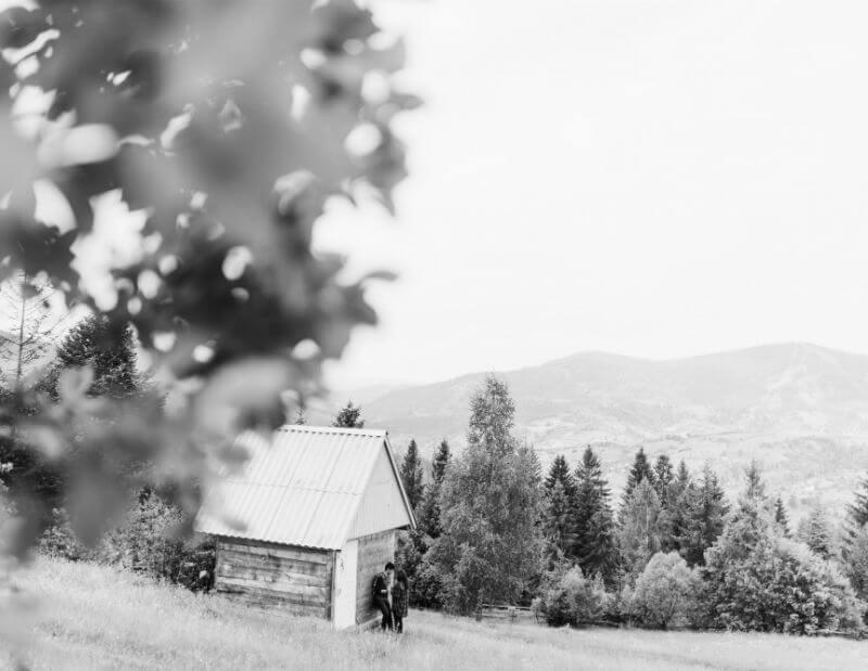 Paar vor idyllischer Holzhütte